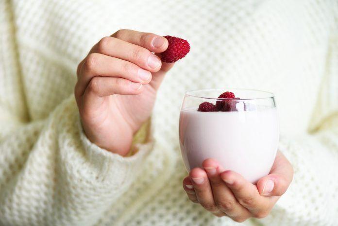 Manos de chica cogiendo vaso de yogur