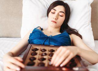 Mujer en la cama comiendo bombones