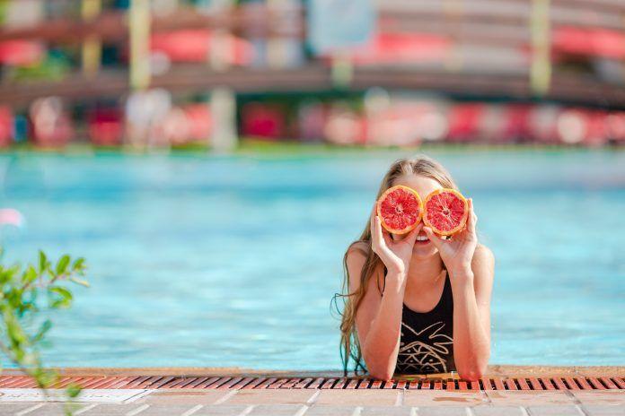 chica en la pisicna tapándose los ojos con un pomelo partido
