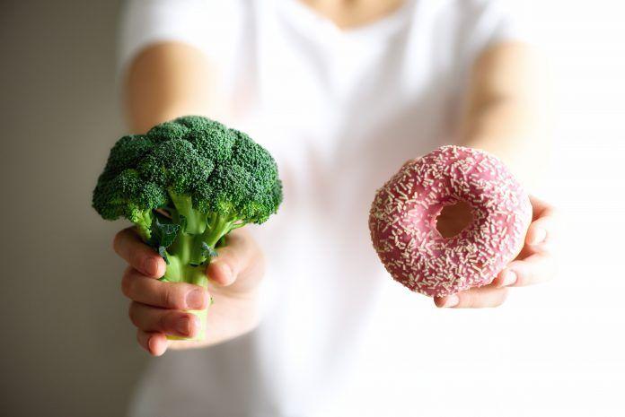 chica cogiendo donut y brocoli